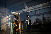 A Chinese engineer from Sepco walks in while an Indian guard walks out of the Chinese office at the construction site of the Adani Power plant of 4620 MW capacity in Mundra port industrial city of Gujarat, India. Indian power companies have handed out dozens of major contracts to Chinese firms since 2008. Adani Power Ltd have built elaborate Chinatowns to accommodate Chinese workers, complete with Chinese chefs, ping pong tables and Chinese television. Chinese companies now supply equipment for about 25% of the 80,000 megawatts in new capacity.