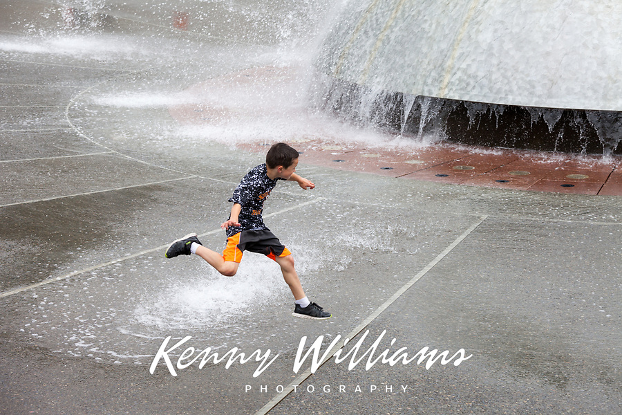 Boy jumping over water fountain spray, Northwest Folklife Festival 2016, Seattle Center, Washington, USA.