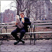 Man in suit sitting on park bench holding the newspaper and eating a banana