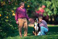 Couple posing with their greater swiss mountain dog.