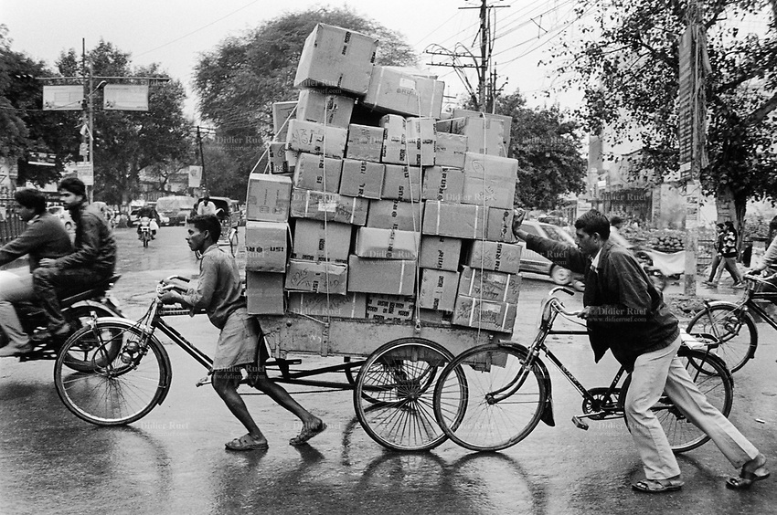 India. Uttar Pradesh state. Allahabad. Two indian Hindus men push a cycle rickshaw heavy loaded with cardboard boxes.Traffic on on a busy road. Uttar Pradesh (abbreviated U.P.) is a state located in northern India. 15.02.13 © 2013 Didier Ruef