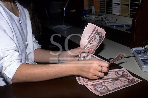 Budapest, Hungary. Woman counting Hungarian money - Forints; 5000 notes.