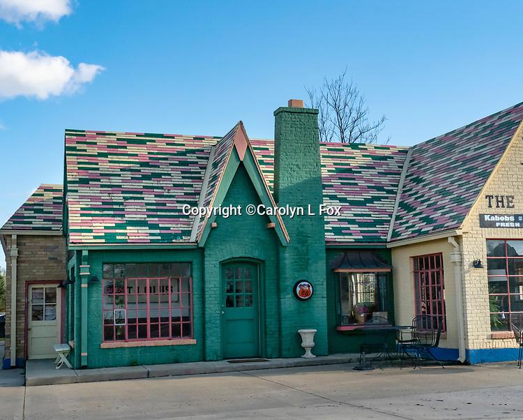 An old green building stands near a street.