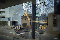 """Switzerland. Canton Ticino. Lugano. Restaurant window with a large clock. A woman wears a mask on the face to protect herself from the Coronavirus (also called Covid-19). She walks alone in the street and holds in her hand a letter which she will drop in the mailbox. Due to the spread of the coronavirus (also called Covid-19), the Federal Council has categorised the situation in the country as """"extraordinary"""". It has issued a recommendation to all citizens to stay at home, especially the sick and the elderly. The Federal Council (German: Bundesrat, French: Conseil fédéral, Italian: Consiglio federale, Romansh: Cussegl federal) is the seven-member executive council that constitutes the federal government of the Swiss Confederation. From March 16 the government ramped up its response to the widening pandemic, ordering the closure of bars, restaurants, sports facilities and cultural spaces. Only businesses providing essential goods to the population – such as grocery stores, bakeries and pharmacies – are to remain open. 23.03.2020 © 2020 Didier Ruef"""