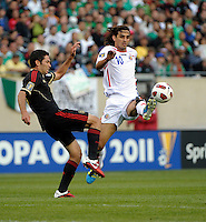Costa Rica's Bryan Ruiz leaps to play the ball in front of Mexico's Israel Castro.  Mexico defeated Costa Rica 4-1 at the 2011 CONCACAF Gold Cup at Soldier Field in Chicago, IL on June 12, 2011.