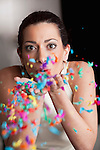 Woman blowing confetti of her hands