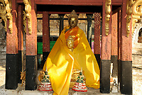 Two sitting statues of Buddha painting in gold color and covered with an orange robe in Wat Phra That lampang Luang, a Buddhist temple in Lampang in Lampang Province, Thailand, Southeast Asia.