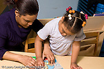 Education Preschool 3-4 year olds female teacher helping girl work on puzzle horizontal