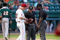 Umpires Ray Valero, left, and James Jean check the glove of starting pitcher Brandon Walter (37) of the Greenville Drive in a game against the Greensboro Grasshoppers on Tuesday, July 20, 2021, at Fluor Field at the West End in Greenville, South Carolina. (Tom Priddy/Four Seam Images)