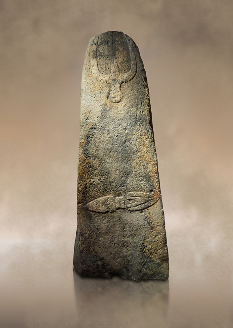 Late European Neolithic prehistoric Menhir standing stone with carvings on its face side. The representation of a stylalised male figure starts at the top with a long nose from which 2 eyebrows arch around the top of the stone. below this is a carving of a falling figure with head at the bottom and 2 curved arms encircling a body above. at the bottom is a carving of a dagger running horizontally across the menhir.  Excavated from Piscina 'E Sali V site,  Laconi. Menhir Museum, Museo della Statuaria Prehistorica in Sardegna, Museum of Prehoistoric Sardinian Statues, Palazzo Aymerich, Laconi, Sardinia, Italy