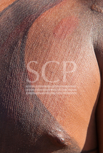 Xingu Indigenous Park, Mato Grosso, Brazil. Aldeia Matipu. Preparing for the Kuarup ceremony Genipapo body paint and scarified chest.