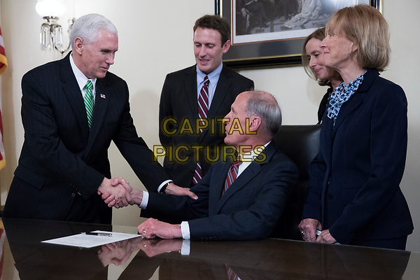 Director of National Intelligence Dan Coats (C), with his wife Marsha Coats (R) and family members, shakes hands with United States Vice President Mike Pence (L)during a swearing in ceremony in the US Capitol in Washington, DC, USA, 16 March 2017.<br /> CAP/MPI/RS<br /> ©RS/MPI/Capital Pictures