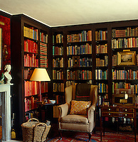A comfortable wing-backed armchair upholstered in a checked fabric stands in a corner of this book-lined library