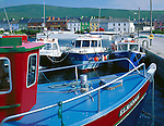 County Kerry, Ireland<br /> Fishing boats docked in Portmagee Channel with the town of Portmagee in the background