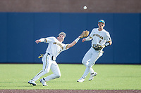 Michigan Wolverines third baseman Christian Molfetta (14) makes a catch as shortstop Benjamin Sems (2) looks on against the Michigan State Spartans on March 22, 2021 in NCAA baseball action at Ray Fisher Stadium in Ann Arbor, Michigan. Michigan State beat the Wolverines 3-0. (Andrew Woolley/Four Seam Images)