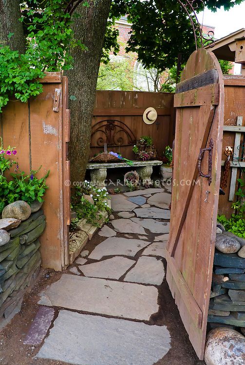 Dress up a rustic fence with rustic ornaments, open door inviting into secret secluded charming garden with flagstone path walkway and bench . Board and batten door