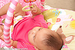 5 month old baby girl seen from behind in infant seat grasping hanging toys