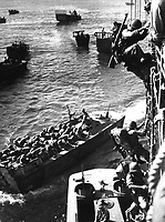 U.S. troops go over the side of a Coast Guard manned combat transport to enter the landing barges at Empress Augusta Bay, Bougainville, as the invasion gets under way.  November 1943. (Coast Guard)<br /> Exact Date Shot Unknown<br /> NARA FILE #:  026-G-3183<br /> WAR & CONFLICT BOOK #:  1164