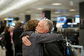A man is embraced after arriving from Dubai on a 14-hour flight on Emirates flight 231, at the international terminal at Dulles International Airport in Dulles, Va., Monday, March16, 2020. Some people are taking the precaution of wearing face masks as they arrive to be greeted by family and or friends. Credit: Rod Lamkey / CNP