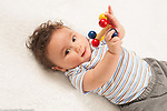 6 month old baby boy on back holding toy and smiling toward viewer