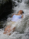 A yoga instructor relaxes in a waterfall outside Cali, Colombia..