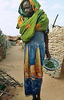 Sudan. West Darfur. Ryiadh. Ryiadh is located on the outskirts of the town of Al Geneina and is a camp for internally displaced people (IDP)) from the civil war. An elderly woman, wearing a fashionable dress with skyscrapers pattern and a veil on her head, lives in poverty. © 2004 Didier Ruef