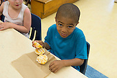 MR / Schenectady, NY. Zoller Elementary School (urban public school). Kindergarten classroom. Boy (5, African American) with fresh fruit (an orange) at snack time. MR: Ste14. ID: AM-gKw. © Ellen B. Senisi.