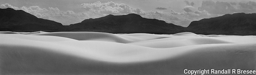 """""""New Mexico Waves"""" <br /> White Sands National Monument, New Mexico <br /> <br /> This scene provided an opportunity to contrast dark mountains with the bright sand at White Sands National Monument. The composition suggests that the natural formations were like waves flowing across the landscape. Of course, constantly changing sand dunes are exactly that but in a slow time scale. Proper exposure and development of the film were critical to this image since the dark mountains and bright sand both required good detail."""