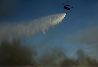 Pictured: A fire helicopter douses the flames with water.<br /> Re: A forest fire has been raging in the area of Kalamos, 20 miles east of Athens in Greece. There have been power cuts, country houses burned and children camps evacuated from the area.
