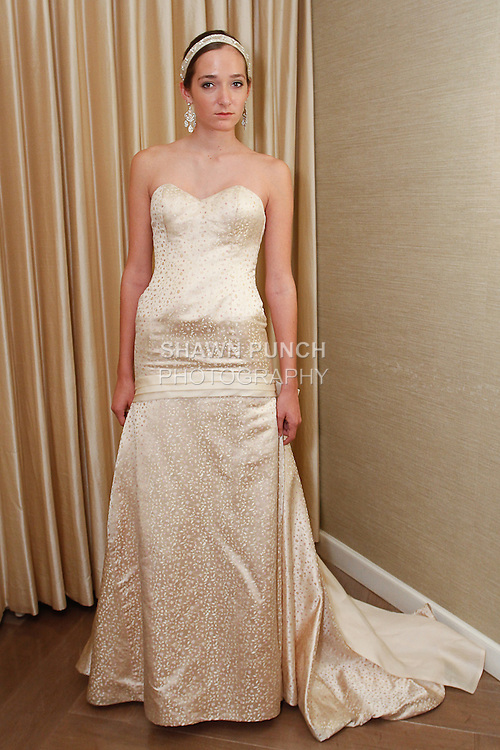 Model poses in a Marianne wedding gown from the Pixton Couture Bridal Spring 2014 collection, by Kimberly Pixton Millar, during New York Bridal Market Week Spring 2014.