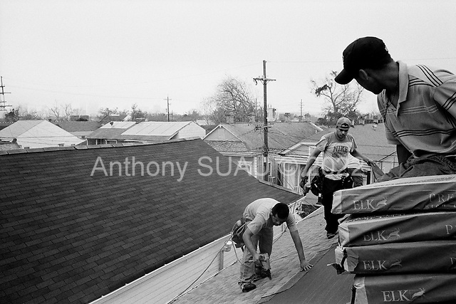 New Orleans, Louisiana.USA.February 21, 2006..Mexican workers replacing roofing to homes in the 7th ward shotgun houses that were damaged when the levees broke in New Orleans and flooded 75% of the city after hurricane Katrina in August 2005......