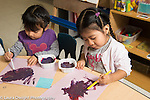 Education Preschool 3-4 year olds art activity two girls painting side by side one using right hand to hold brush the other the left hand