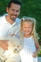 Father and young daughter playing with bichon frise puppy in the park