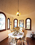 Glendale, California. 1929.  The breakfast nook, the owner's favorite spot, is accented by a domed ceiling covered in roughly patterned plaster.  The chandelier with its art glass shades is original to the room.  Arched, leaded glass windows with mahogany trim let light stream into the room.  The kitchen table and chairs are from the 1930's and again passed down in the owner's family. RELEASED