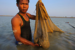 Subsistence shrimper with catch. Rakhine State, Myanmar. January.