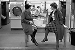 Public Laundry 1970s UK. Women taking their dirty used clothes to a public laundry to get them washed. Woman chatting with friend while waiting for their clothes washing to finish. Battersea south London 1979