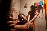 The younger son of The Pehlwan (an Indian wrestler) Jawla Trwatri gives an oil massage to his father in the early morning. Kolkata, India