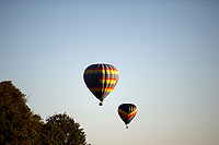 Hot air balloons float over a field near the airport in Bloomington, Indiana on Saturday, Sept. 19, 2020. (Photo by James Brosher)