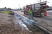 A sealant is sprayed onto fresh concrete  after new curbs were laid on Westerville Road at Dempsey as roadway improvements near completion at the intersection. The changes are part of an improvement project at the I-270 interchange to upgrade the entrance road to Westerville, OH.