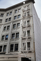 The geometry of a zig-zag fire escape and rectangle windows on a downtown Oakland, California, building.