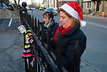 TORRINGTON, CT-122117JS08---Joanne Borders, CEO of Community Health and Wellness Center in Torrington, right, and Patricia Martin, left, tie scarves on the fence across from Trinity Church in Torrington on Thursday. The center received 50 donated scarves and tied 50 them on fences and trees at the church, the YMCA and Coe Park, for anyone who needs one.<br /> Jim Shannon Republican-American