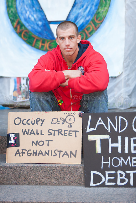"A man sits behind protest signs in Zuccotti Park encouraging ""Occupy Wall Street, not Afghanistan"" during the Occupy Wall Street demonstration in New York City, New York."