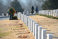 Zackary Jackson of Fayetteville, a veteran of the U.S. Army, collects wreaths Saturday, Jan. 9, 2021, while collecting the holiday wreaths at the Fayetteville National Cemetery. The wreaths were placed in front of each grave in the cemetery in December by volunteers through the Wreaths Across America program and were collected by groups of volunteers organized by the Fayetteville National Cemetery Advisory Council who worked in shifts because of the pandemic. Visit nwaonline.com/210110Daily/ for today's photo gallery. <br /> (NWA Democrat-Gazette/Andy Shupe)