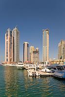 Dubai.  Luxury motor cruisers moored at Dubai Marina with apartment tower blocks in the background..