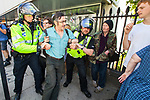 © Joel Goodman - 07973 332324 . 24/04/2011 . Brighton , UK . Police remove an antifascist counter protester who attempts to block the march's route by clinging to a lamppost . Nationalist street movement March for England holds a march and rally in Brighton , opposed by antifascists . Photo credit : Joel Goodman