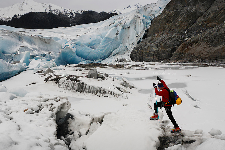 Hiker climbs on top of melting Mendenhall Glacier in Southeast Alaska.