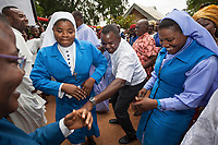 """Nigeria. Enugu State. Agbani. Reverend Father Gerald Chukwudi Ani (C) is a catholic priest from the Diocese of Lugano (Ticino, Switzerland). Back in his homeland, he has organized in the family home a party to celebrate his 10th year anniversary of priesthood and the 5th year of his mother's death. He dances with a group of religious sisters from three various orders """" Daughters of Mary Mother of Mercy"""", """" Daughters of Divine Love"""" and """"Sisters of Jesus the Savior"""". 7.07.19 © 2019 Didier Ruef"""