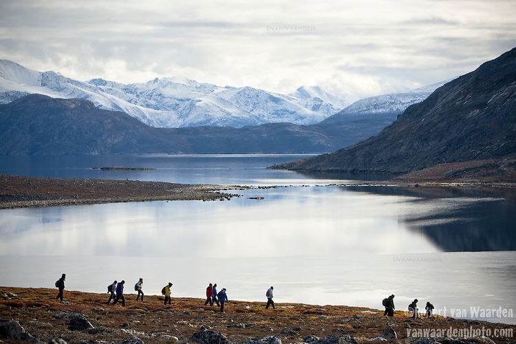 A group of people in an immense landscape, Baffin Island, Nunavut, Canada. In the background, the snow covered mountains of Baffin Island.
