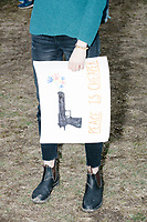 "Students enter Boston Common after marching to the park from Roxby Crossing during the March For Our Lives protest and demonstration in Boston, Massachusetts, USA, on Sat., March 24, 2018. The march was held in response to recent school gun violence. Here, a woman holds a sign with flowers coming out of a pistol and the words, ""Peace is cheaper."""