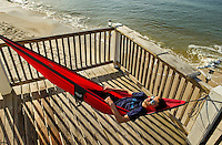 A teenage boy relaxes in a hammock along Dauphin Island, Alabama, a barrier island located three miles south of the mouth of Mobile Bay in the Gulf of Mexico. This island, which is approximately 14 miles long and less than two miles wide, appears to have fully recovered from the impact of Hurricane Katrina (2005) and the BP Deepwater Horizon Oil Spill in 2010. Both events greatly reduced tourism income (fewer people came to the island) and local business owners say many establishments went out of business. Today they say they're looking forward to a rebounding tourism business.